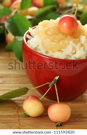 Bowl of rice served with apple sauce and fruits - stock photo