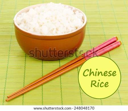 Bowl of rice with chopsticks on bamboo mat and space for your text - stock photo