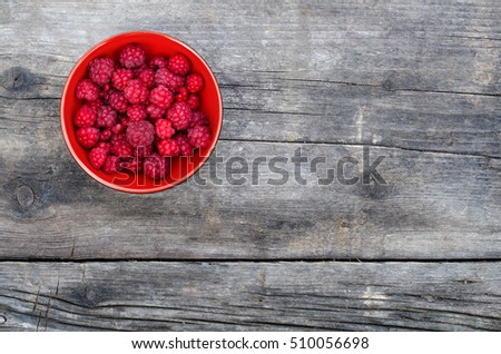 Bowl of ripe red raspberries on wooden table in summer.