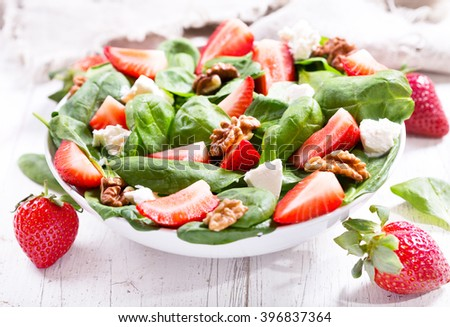 bowl of salad with strawberry, spinach leaves and feta cheese on wooden table - stock photo
