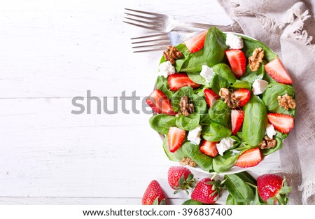 bowl of salad with strawberry, spinach leaves and feta cheese, top view - stock photo