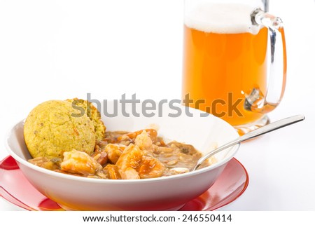Bowl of sausage and shrimp gumbo on with frothy mug of beer and cornbread muffin.  White background with copy space. - stock photo