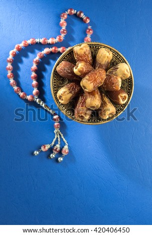 Bowl of scared Arabian date fruits with Islamic prayer beads on bright blue background. - stock photo