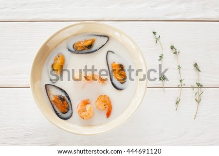 Bowl of seafood cream-soup with rosemary flat lay. Top view on bowl with white cream-soup with mussels and shrimps on white wooden background, decorated with rosemary, void. Creative food decoration - stock photo