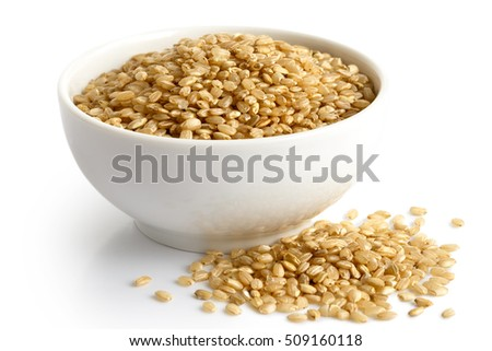 Bowl of short grain brown rice isolated on white. Spilled rice.