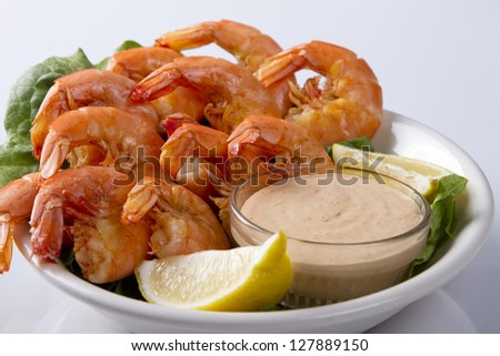 Bowl of shrimp with lemon slices and dipping sauce - stock photo
