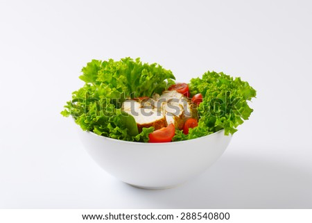 bowl of sliced chicken breasts with lettuce and cherry tomatoes on white background