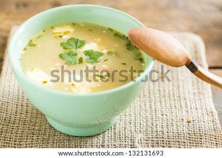 bowl of soup on a vintage table an a wooden spoon