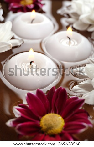 Bowl of spa water with flowers and candles, closeup - stock photo