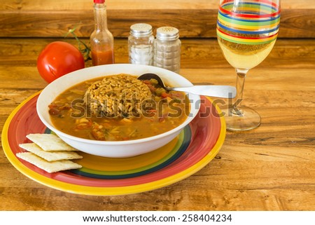 Bowl of spicy Chicken Gumbo on colorful plate with matching glass of white wine.  Sausage Dirty Rice in middle of gumbo. - stock photo