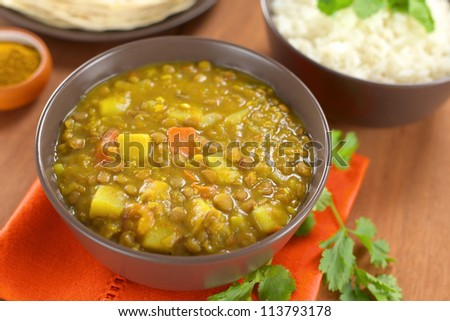 Bowl of spicy Indian dal (lentil) curry prepared with carrot and potato, rice and curry powder in the back and cilantro leaf on the side (Selective Focus, Focus in the middle of the curry) - stock photo
