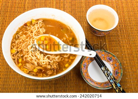 Bowl of spicy noodle soup in Chinese or Asian Setting with colorful dishes and chopsticks.   Overhead view; Sitting on Bamboo Place Mat. - stock photo