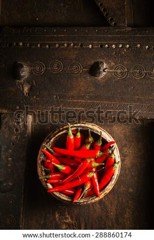 Bowl of spicy pungent red hot cayenne chili peppers for flavoring cooking viewed from overhead on an old rustic wooden table with copyspace - stock photo