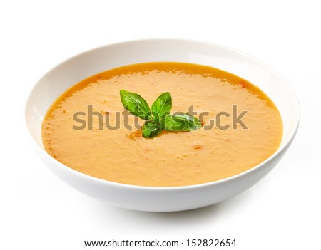 bowl of squash soup with basil leaf isolated on white - stock photo