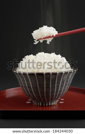 Bowl of steamed rice with chop sticks  - stock photo