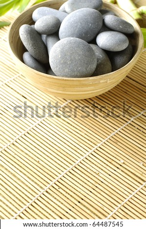 Bowl of stones with green plant on mat - stock photo