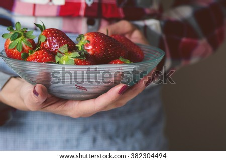bowl of strawberries in the hands of a woman with apron