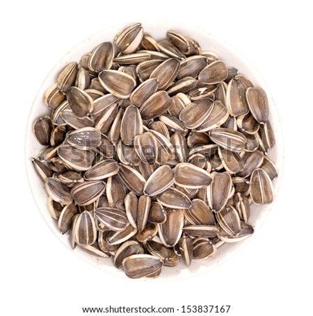Bowl of striped sunflower seeds isolated on white