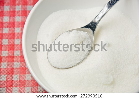 Bowl of sugar with metal spoon - stock photo