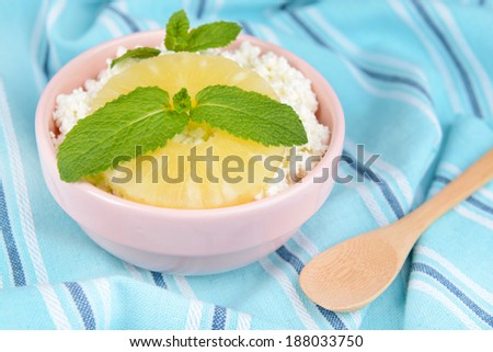 Bowl of tasty cottage cheese with pineapple, close up
