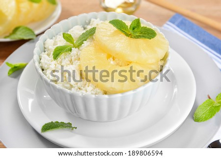 Bowl of tasty cottage cheese with pineapple on wooden table - stock photo
