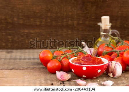 Bowl of tomato sauce with fresh ingredients on wooden background - stock photo