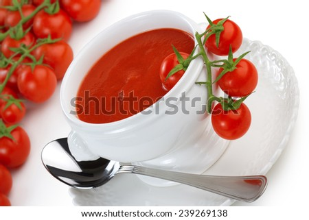 bowl of tomato soup and cherry tomatoes on white background - stock photo