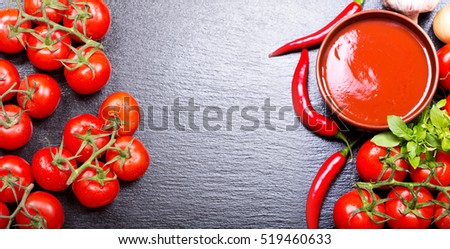 bowl of tomato soup with fresh vegetables on dark background, top view with copy space
