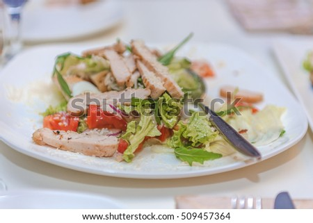 Bowl of Traditional Caesar Salad with Chicken and Bacon on a table