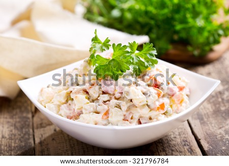 bowl of traditional russian salad on wooden table