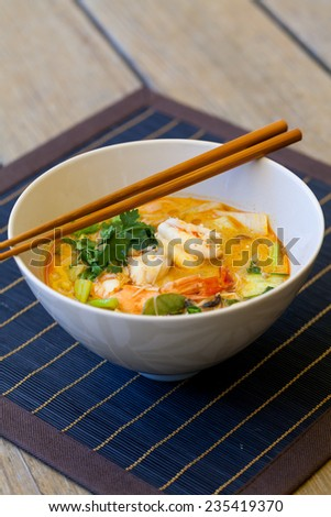 Bowl of traditional Thai tom yam soup with vegetables and prawns in a spicy aromatic broth served with chopsticks