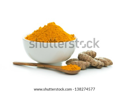 Bowl of turmeric powder with fresh turmeric root