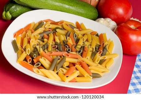 Bowl of uncooked tri-color pasta and ingredients