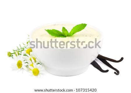 Bowl of vanilla yogurt with vanilla beans and daisy flowers on white - stock photo