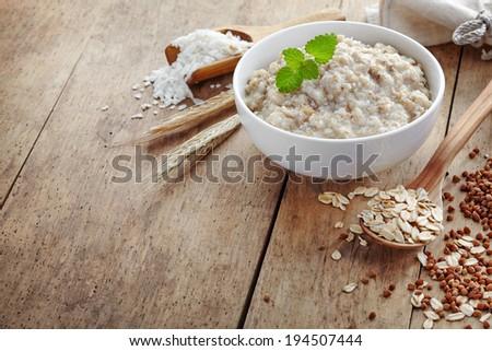 Bowl of various flakes porridge on wooden table - stock photo