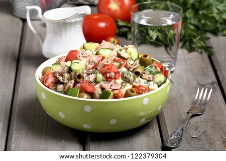 Bowl of vegetable salad on wooden table - stock photo