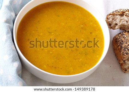 Bowl of vegetable soup with bread on side, placed on white table cloth - stock photo