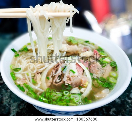 Bowl of Vietnamese pho noodle soup with rare beef, tendon, tripe and brisket served with onions, scallions and cilantro. - stock photo