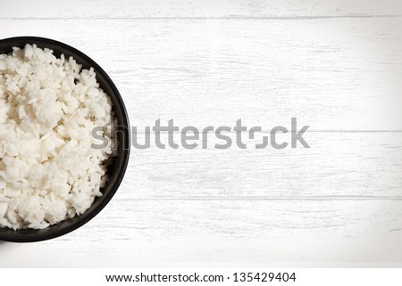 Bowl of white rice on white wood grain background with copy space. - stock photo