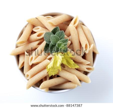Bowl of whole wheat pasta tubes - overhead - stock photo