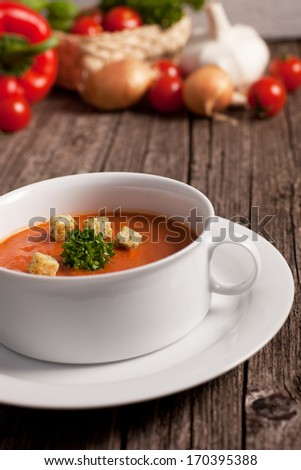 Bowl of wholesome vegetable soup garnished with fresh parsley and crispy fried croutons on a rustic wooden surface with vegetable ingredients visible in the background