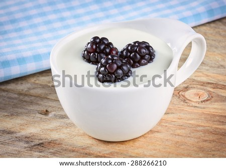 Bowl of yogurt and fresh Blackberries served on a wooden table - stock photo