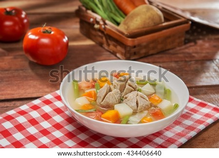 Bowl soup of vegetables and beef balls on the table in restaurant - stock photo