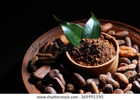Bowl with aromatic cocoa harvest on wooden background, close up - stock photo