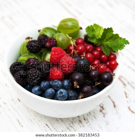 bowl with berries on a old wooden background