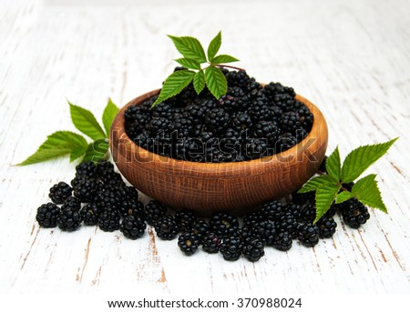 Bowl with Blackberries on a old wooden background - stock photo