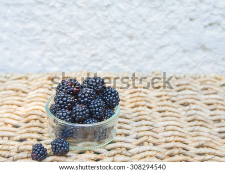 Bowl with Blackberry on wicker background. Background with space for text. - stock photo