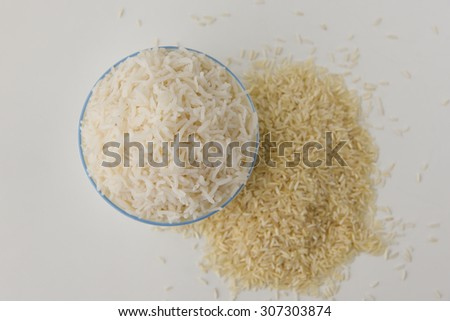 bowl with boiled or cooked white rice and raw white rice scattered on white background. basmati or jasmine rice used to prepare biriyani or pulav in India.uncooked long grain rice lying scattered - stock photo