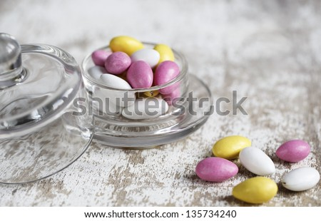 Bowl with bright pink, yellow and white sweet candy bonbons