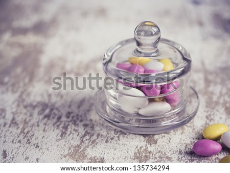 Bowl with bright pink, yellow and white sweet candy bonbons - stock photo